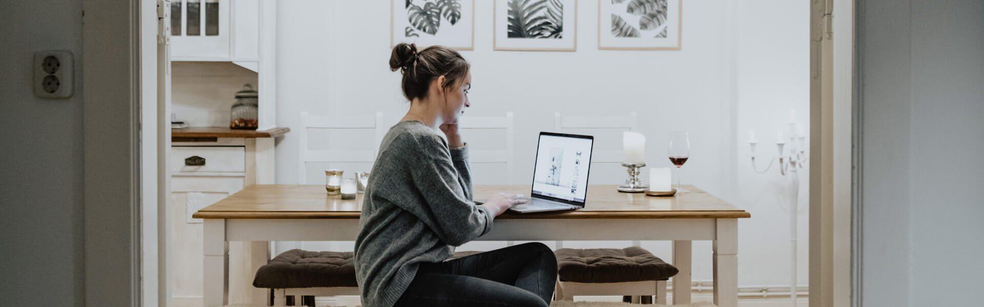 Frau arbeitet in der Küche am Laptop